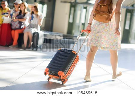 The girl at the station. Behind shoulders a backpack in hands a suitcase. View from a back.