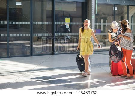 Young cheerful tourists hurry on the flight. Girls have an excellent mood. Summer vacation.