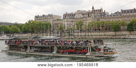 ParisFrance- April 29 2017: On the river Seine sailing ship with cheerful tourists