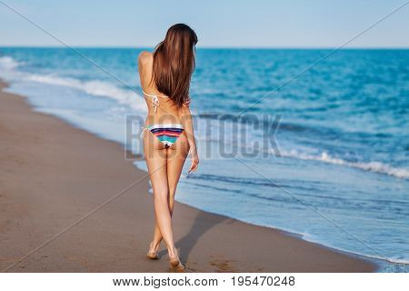 Sexy Back Of A Beautiful Woman In Bikini On Sea Background. Sexy Buttocks. Soft Sunset Light.
