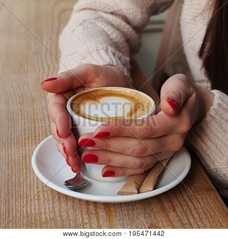 Close-up Female Hands Holding Cup With Coffee Cappuccino With Foam With Pattern Heart. Perfect Red G