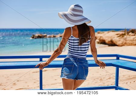 Portrait Of Beautiful Tanned Woman At The Sea Coast In Hat And Retro Style Clothes. Hot Summer Day A