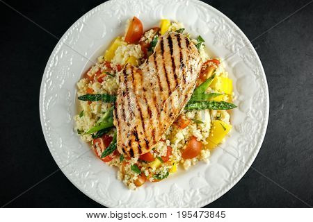 couscous salad with grilled chicken and asparagus on white plate. stone table. healthy food.