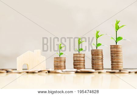 wooden house model and step of coins stacks with tree growing on top loft style background money saving and investment or family planning concept.