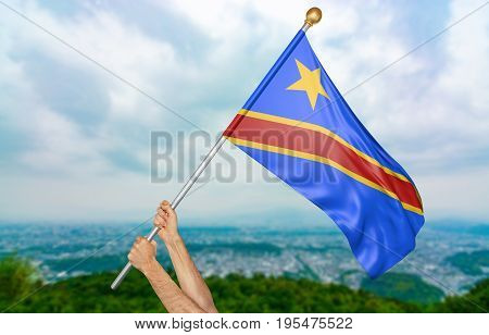 Young man's hands proudly waving the DR Congo national flag in the sky, part 3D rendering