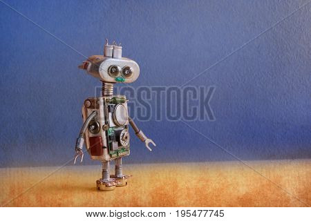 Robotic ufo alien toy with lamp bulb eyes, metallic springs hands, blue yellow futuristic background. Copy space