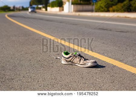Poverty concept - Thrown out on the street dirty ragged sneaker.