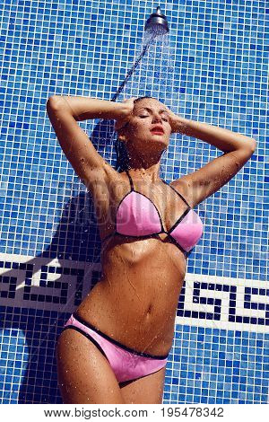 Beautiful tanned young woman with perfect body wearing pink bikini taking shower. outdoor shot. copy space.