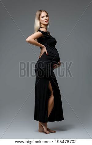 Beautiful pregnant young woman in long black dress. Studio portrait on grey background. Copy space.