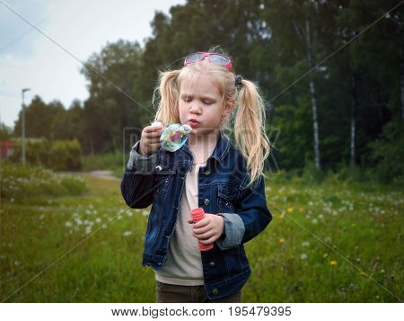 Girl inflates soap bubble. Portrait of a child. Long blonde hair beautiful face. Nature field green grass forest
