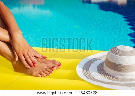 Portrait Of Beautiful Tanned Woman Relaxing In Swimming Pool. Hat And Inflatable Matress. Legs And H