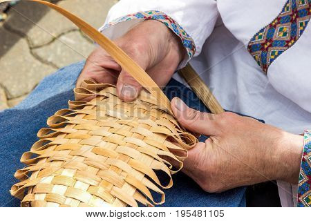 male hands plaiting bast shoe. Culture of Belarus