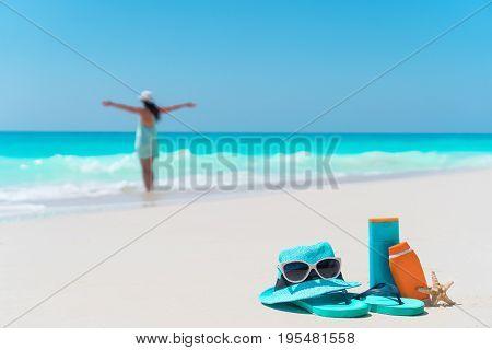 Suncream bottles, goggles, starfish on white sand background ocean