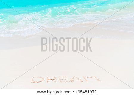 Word Dream handwritten on sandy beach with soft ocean wave on background