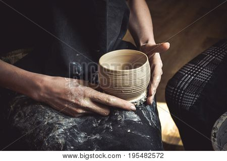 A raw clay pot in the hands of a potter. Master crock.