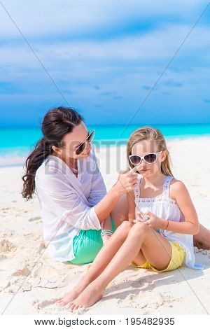 Young mother applying sun cream to daughter nose on the beach