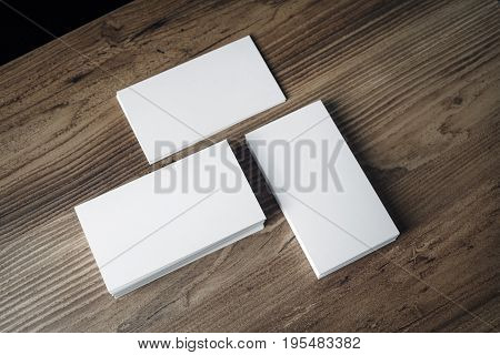 Piles of blank business cards on wood table background. Blank stationery. Mock up for branding identity for placing your design. Top view.