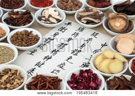 Chinese medicinal herb selection with calligraphy script. Translation reads as chinese herbal medicine as increasing the bodys ability to maintain body and spirit health and balance energy.