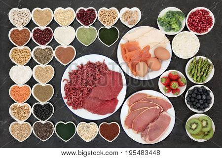 Body building health food with meat, fish, supplement powders, dairy, fruit, vegetables, pulses, nuts, seeds, grains and cereals on porcelain plates.