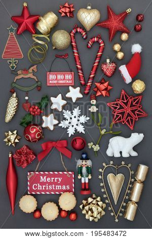 Symbols of christmas with bauble decorations, holly, mistletoe, mince pies, gingerbread biscuits and signs on grey background.