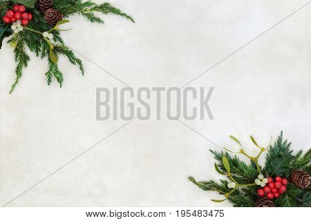 Winter and christmas background border with holly, mistletoe, ivy, juniper fir and pine cones on old parchment paper.