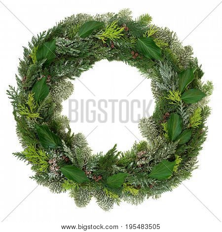 Winter and Christmas wreath decoration with snow covered natural juniper fir, blue spruce, cedar and ivy leaves on white background.