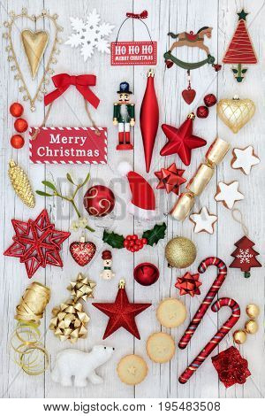 Symbols of christmas with bauble decorations, holly, mistletoe, mince pies, gingerbread biscuits and signs on distressed white wood background.