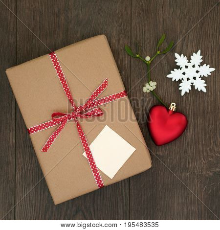 Christmas gift box wrapped in brown paper, tag, red ribbon with mistletoe, heart and snowflake bauble decorations on oak background. Top view.