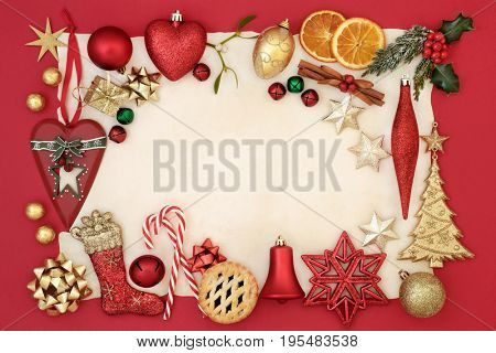 Abstract christmas border with bauble decorations, holly, mistletoe, fir, dried orange and mince pie on parchment paper and red background.