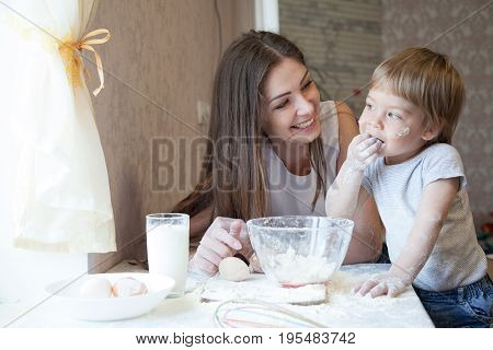 mother and young son prepare a cake in the kitchen 1