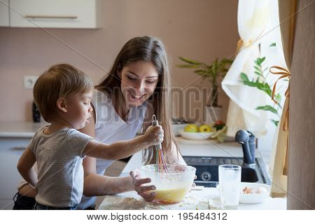 mother and young son prepare pie in the kitchen 1