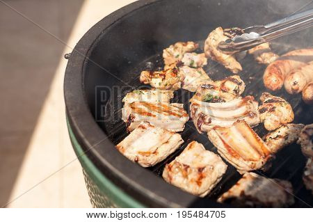food, picnic, recipes and meat concept - closeup on a delicious cooking pork ribs grill pan along with the sausages, turning pieces for even roasting by metal kitchen tongs, sunny festive day on lawn