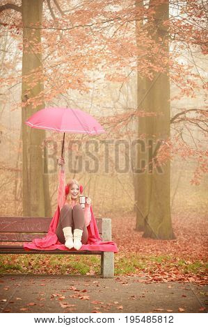 Happiness carefree and fall concept. Joyful woman relaxing in autumn park on bench under umbrella enjoying hot drink holding thermal mug with warm beverage. Orange leaves background
