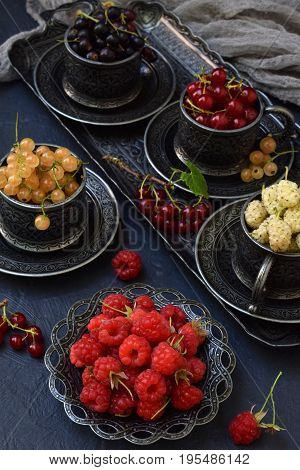Composition Of Fresh Ripe Berries: Red, Black And White Currant, Mulberry On A Dark Gray Concrete Ba
