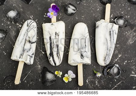 Yoghurt refreshing marble ice cream popsicle in trendy fashion colors on a dark background with edible flowers of garden violas. Selective focus. Top View.