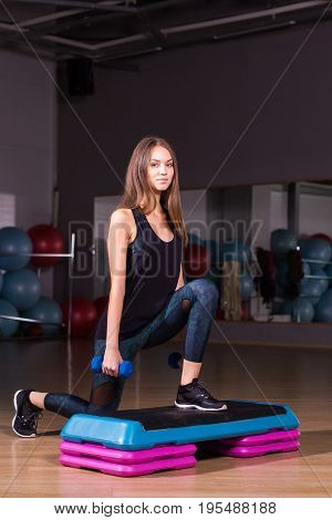 Fitness step, training, aerobics, sport concept - Athletic woman trainer at step doing aerobic with steppers indoors. Fitness woman with step platform doing workout
