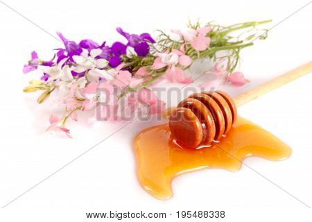 Honey stick with flowing honey and wildflowers isolated on white background.
