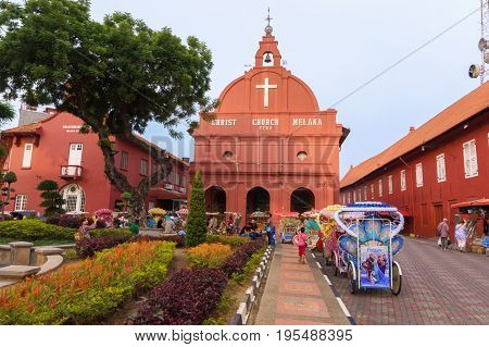 Melaka Malaysia - April 20 2017: The scenery at Dutch Square Melaka or Malacca, Malaysia with famous Christ Church building and colorful trishaws for tourists visiting Melaka.