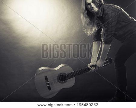Rock music energy people feelings concept. Mad rock guitarist destroys his guitar.