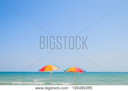 Blurred image of beach chair and umbrella on sand beach