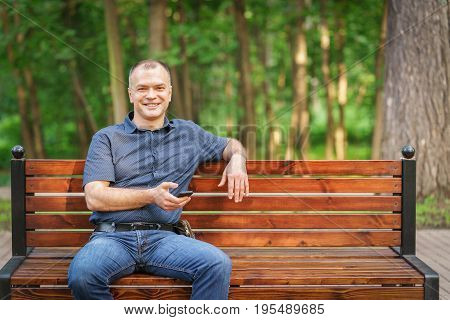 Adult Man Around 35-40 Is Sitting With Smile And Phone On The Bench Atsummer Park