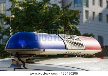 blue and red siren of police car on the city street at summer day time with buildings background
