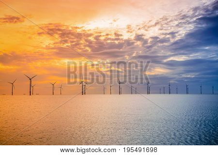 Sunset Offshore Wind Turbine in a Wind farm under construction of England coast UK