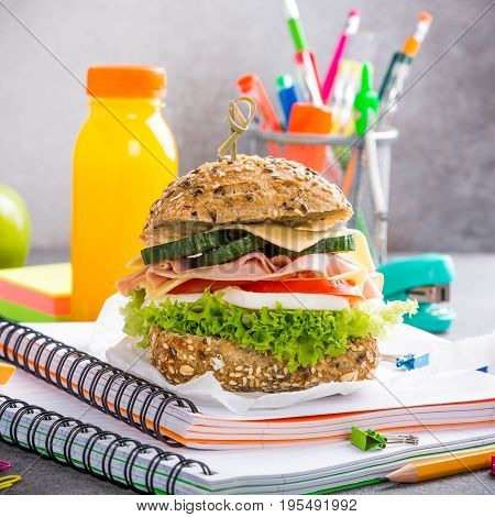 Healthy lunch for school with sandwich, fresh apple and orange juice. Assorted colorful school supplies.
