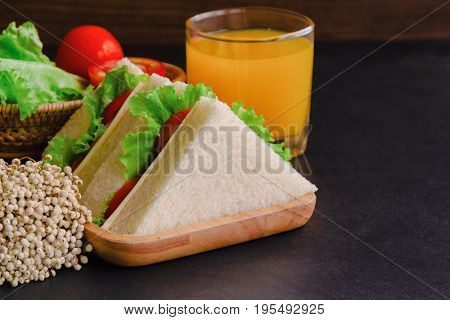 Piece of sandwich ham cheese with lettuce and tomato on wood plate. Homemade sandwich served with orange juice for breakfast or lunch. Delicious ham cheese sandwich ready to served on granite table. Triangle slice sandwich ham and cheese.