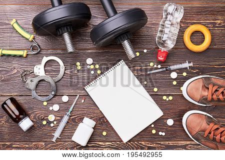 Paper notebook, syringe, dumbbells, handcuffs. Illegal pills in sport activity.