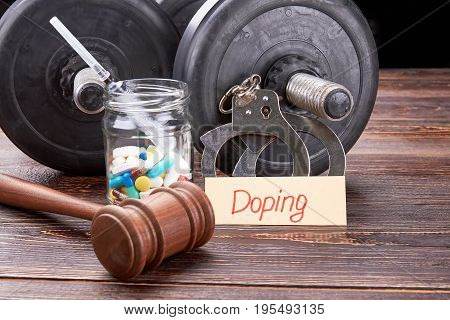 Gavel, colorful pills, syringe, dumbbells. Message doping, handcuffs, pills, syringe, dumbbells on wooden background. Illegal medicine in sports activity.