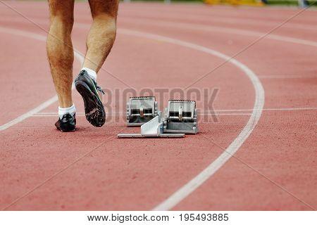 feet men runner sprinter track and starting blocks