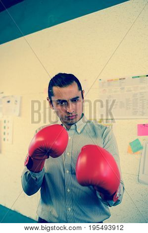 businessman with boxing gloves punch to camera in the office vintage style