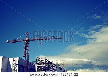 Hoisting crane. Beautiful clouds. Construction. Unfinished building.